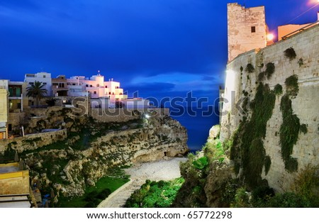 "Night view of little village ""Polignano a mare"" with it's bay and tower - stock photo"