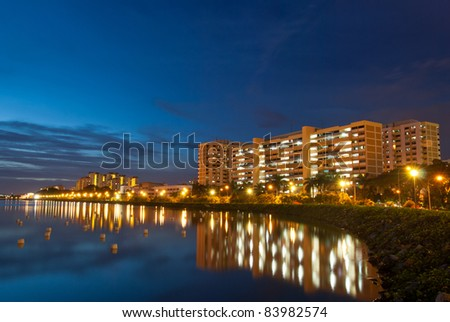 Night view of peaceful residential district with reflection in lake. - stock photo