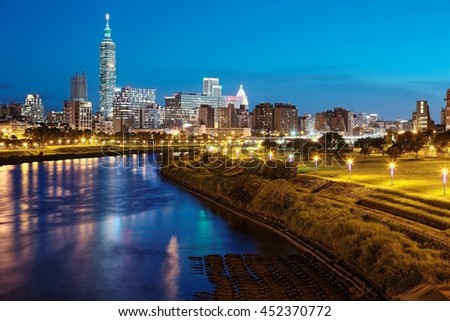 Night view of Taipei City by riverside with skyscrapers and beautiful lights reflecting on smooth water ~ Landmarks of Taipei 101 Tower, Keelung River & Xinyi District in downtown area at dusk - stock photo