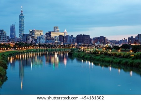 Night view of Taipei City by riverside with skyscrapers and beautiful reflections on smooth water ~ Landmarks of Taipei 101 Tower, Keelung river, Xinyi district and downtown area at dusk - stock photo