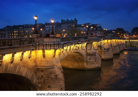 Night view of the Bridge au Change over river Seine and Conciergerie - a former prison in Paris, France, located on the Island of the City - stock photo