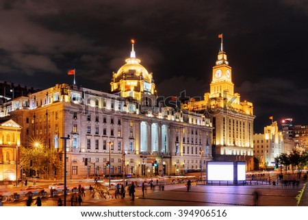 Night view of the Bund (Waitan) in Shanghai, China. The Shanghai Custom House building with clock tower is visible at right, the HSBC Building (the Municipal Government Building) at left. - stock photo