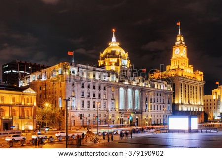 Night view of the Bund (Waitan), Shanghai, China. The Shanghai Custom House building with clock tower is visible at right, the HSBC Building (the Municipal Government Building) at left. - stock photo