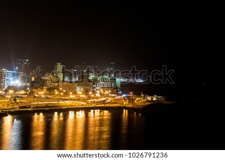 Night view of the coastline profile of Havana in Cuba with the lights of the city reflecting in the bay