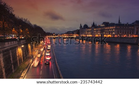 Night view of the Conciergerie - a former prison in Paris, France, located on the Island of the City. With river Seine, cars at the highway and Bridge au Change - stock photo