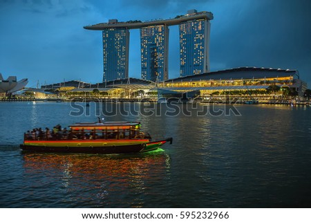 Night view of the glowing waterfront with Marina Bay Sands hotel in Singapore. There is a floating boat on the foreground. Horizontal.
