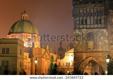 Night view of the Gothic tower and distant church dome, Prague, Czech Republic - stock photo