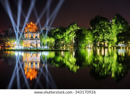 Night view of the Hoan Kiem Lake (Lake of the Returned Sword) and the Turtle Tower among blue light rays at historic centre of Hanoi in Vietnam. The tower reflected in the lake.