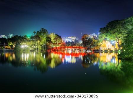 Night view of the Huc Bridge (Morning Sunlight Bridge) on the Hoan Kiem Lake (Lake of the Returned Sword) in historic centre of Hanoi, Vietnam. The bridge reflected in the lake. - stock photo