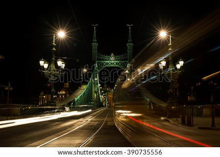 Night view of tram and cars crossing Liberty Bridge in Budapest, Hungary, Pest side of the city - stock photo