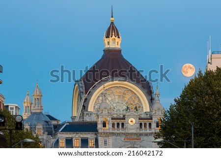 Night view on the dome of the exterior of Antwerp central railway station at dusk, with deep blue sky and a bright shining moon - stock photo