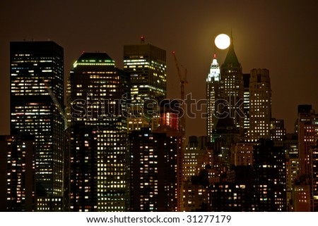 night vision of the top of toll buildings in lower Manhattan during full moon in middle of the night - stock photo