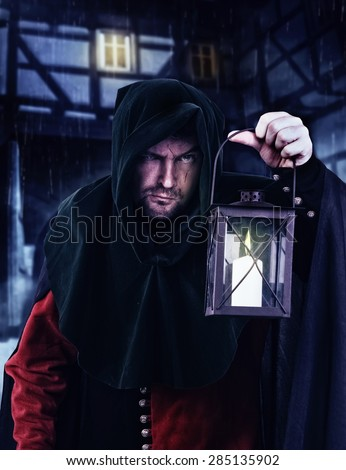Night watchman in a medieval suit and hood with a lantern  - stock photo