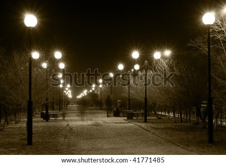 night winter city lane with burning street lamps in sepia tone - stock photo