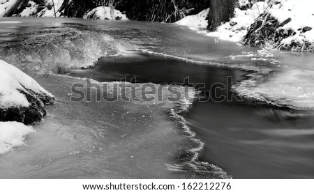 Night winter view to frozen brook, icy twigs and icy boulders above rapid stream. Reflections of light in icicles. Black and white photo. Extreme freeze. - stock photo