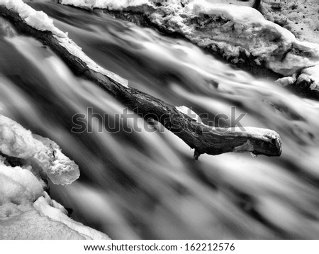 Night winter view to frozen cascade of waterfall, icy twigs and icy boulders in frozen foam of rapid stream. Reflections of light in icicles. Black and white photo. Extreme freeze. - stock photo