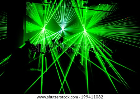 Nightclub party ravers with hands in the air and green lasers silhouette - stock photo