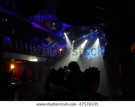 Nightclub scene with laser light show and dance floor crowd in motion