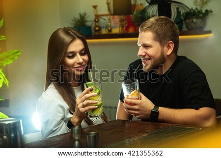 Nightlife concept. Man flirting with beautiful woman in the bar with alcoholic cocktails - stock photo