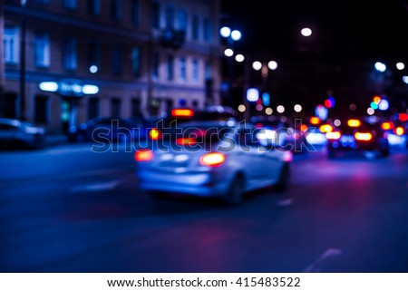 Nights lights of the big city, the city street with cars riding on it. Defocused image, in blue tones