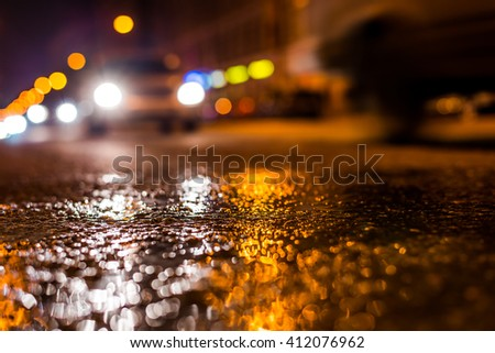 Nights lights of the big city, the night avenue with driving cars. Close up view from the level of asphalt, focus on the asphalt - stock photo