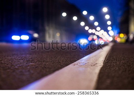 Nights lights of the big city, the night avenue with road markings and headlights of the approaching cars, close up view from asphalt level. In blue tones - stock photo