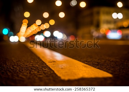 Nights lights of the big city, the night avenue with road markings and headlights of the approaching cars, close up view from asphalt level - stock photo