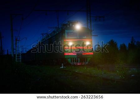 Nighttime shot of an electric train crossing the Russian countryside near Polyarnye Zori, Murmansk, Russia. - stock photo
