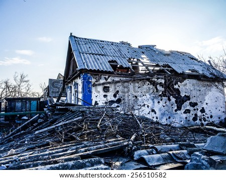 NIKISINO, UKRAINE - Feb 27, 2015: Ruined house. Village Nikishino located 20 km from Debaltseve, Ukrainian military was abandoned three days ago. Separatist forces attacked it for several days.  - stock photo
