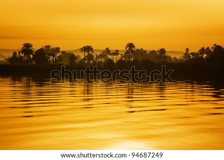 Nile view at sunset with tropical palm tree silhouette and distant mountains - stock photo