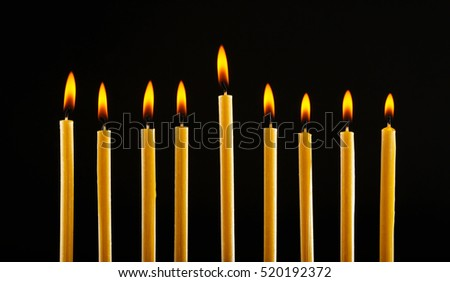 Nine burning candles on black background. Hanukkah concept