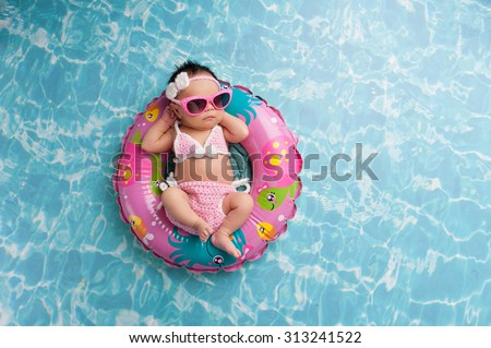 Nine day old newborn baby girl sleeping on a tiny inflatable swim ring. She is wearing a crocheted pink and white bikini and pink sunglasses. - stock photo