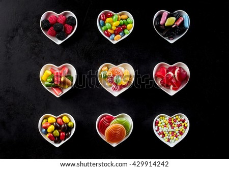 Nine heart shaped white bowls in rows of three filled with hard candies, licorice rolls, gum drops and jelly beans - stock photo