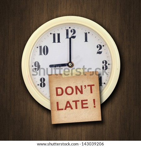 nine o'clock on the wall clock  with the old paper short note and text don't late on wood background - stock photo