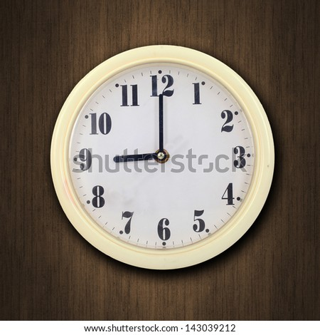 nine o'clock on the wall clock  wood background - stock photo