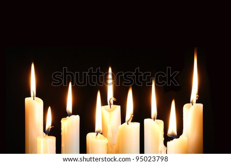 Nine ordinary lighting candles in a row on black background - stock photo