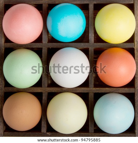 Nine pastel  easter eggs in a printers box - stock photo