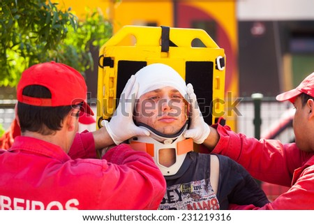 NINE, PORTUGAL - APRIL 12, 2014: Emergency crew immobilizes victim with a cervical collar in a stretcher during a simulated train accident