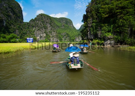 NINH BINH, VIETNAM - MAY 27: Unidentified travellers with rower guides in a boat trip visiting Tam Coc on May, 27, 2014 in Ninh Binh, Vietnam. Tam Coc is the destination of Ninh Binh Province.