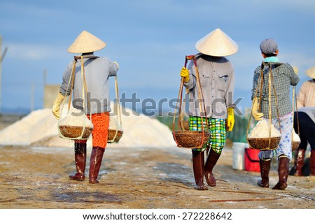 NINH HOA, VIETNAM - MARCH 2, 2012: Women are working very hard to collect salt from the extract fields to the storage house - stock photo