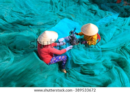 Ninh Thuan Province, Vietnam - February 27, 2016: two women are sewing fishing nets in fishing village in Vinh Hy Bay, Phan Rang province. They work hard all day to sew large fishing nets