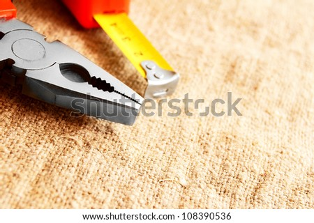 Nippers and a measuring roulette on a fabric . - stock photo