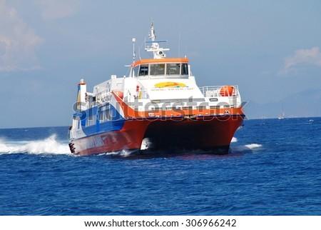 NISYROS, GREECE - JUNE 9, 2015: Dodekanisos Seaways catamaran ferry Dodekanisos Express arriving at Mandraki harbour on the Greek island of Nisyros. The 40mtr vessel was built in Norway in 2000. - stock photo