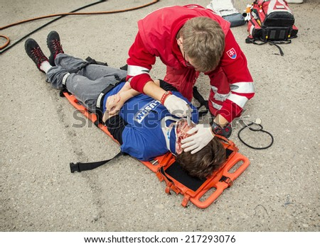 Nitra, Slovakia - September 06, 2014: Simulation of the car accident. Emergency service worker makes the control of vital functions. - stock photo
