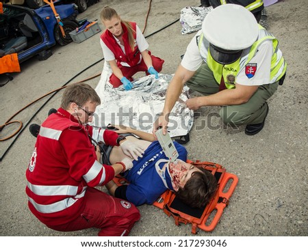 Nitra, Slovakia - September 06, 2014: Simulation of the car accident. Paramedics stabilizing the patient. Policeman makes the breath test for alcohol. - stock photo