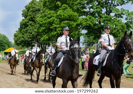 NIURONYS, LITHUANIA - JUNE 01: Ranger police riders show in annual city horse festival and people public audience on June 01, 2013 in Niuronys, Lithuania.  - stock photo