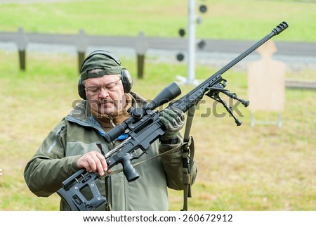 Nizhniy Tagil, Russia - September 25. 2013: Display of weapon with demonstration of firing on shooting ground. Representative of firm shows sniper rifle ORSIS T-5000 - stock photo