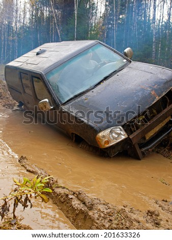 NIZHNY TAGIL. RUSSIA - JUNE 12, 2013: Russian Plain Road in the heart of Siberia. Wheel drive vehicle leaves the swamp - stock photo