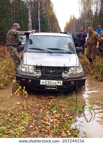 NIZHNY TAGIL. RUSSIA - SEPTEMBER 22, 2012: Men try to pull out of the swamp a failed car. Russian Plain Road in the heart of Siberia - stock photo