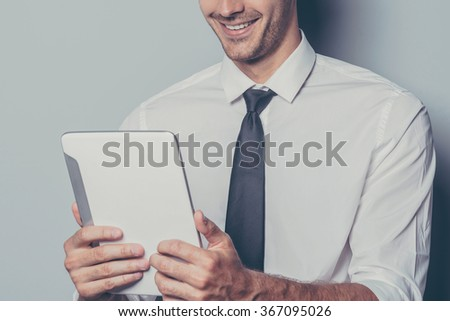 njoying his new digital tablet. Cropped image of cheerful young man holding digital tablet and smiling while standing against grey background - stock photo